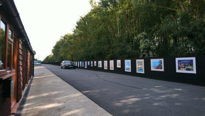 Black Jaguar car driving past an open air art exhibition